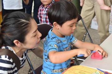 歯の模型を真剣な表情で磨く子ども=長崎市、JR長崎駅かもめ広場