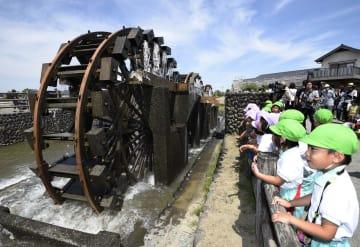 福岡県朝倉市で、稲作の季節を迎えて回り始めた「三連水車」=17日午前