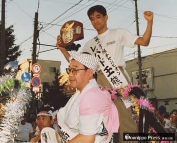 世界王者を獲得し地元・青森市に凱旋したレパード玉熊に付き添う高橋会長(手前)=1990年8月2日