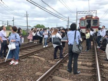 近鉄京都線の車両から降り、線路上に避難する乗客ら(18日午前9時半、京都市伏見区)
