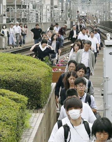 停止した電車から降りて阪急宝塚線の線路を歩く人たち=18日午前10時23分、大阪府池田市