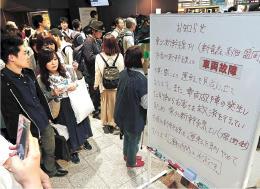 東北新幹線の運転見合わせを知らせる掲示板に見入るJR仙台駅の利用客=17日午後5時ごろ