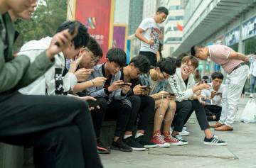 中国・天津市のショッピングモールの前で、スマートフォンのゲームで遊ぶ若者ら=2017年10月1日(ゲッティ=共同)