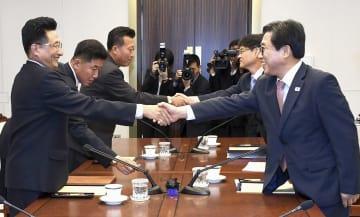 18日、板門店で握手する韓国の全忠烈・大韓体育会事務総長(手前右)と北朝鮮の元吉友体育次官(韓国文化体育観光省提供・聯合=共同)