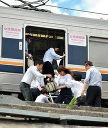 JR西日本の社員らに誘導され、はしごを使って電車を降りる乗客=18日午前、西宮市六湛寺町(撮影・岡西篤志)