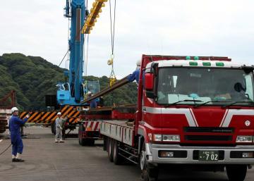 トレーラーに載せられる、九州新幹線長崎ルートで使用するレール=佐世保港(鉄道・運輸機構提供)