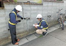 ブロック塀の損傷状態を調べる東北工大の学生。災害時の倒壊リスクが懸念されている=2014年、仙台市内(東北工大提供)