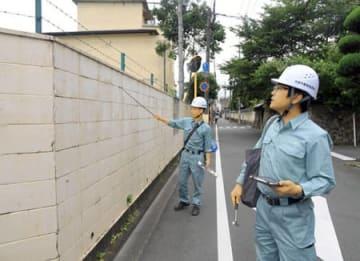 中学校の塀を点検する京都市教育委員会の職員(19日午前9時56分、京都市上京区・烏丸中)