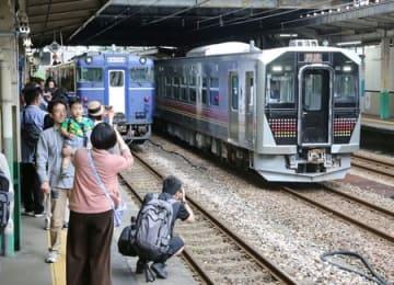 柳都Shu*Kura(左)と並んで停車する電気式気動車「GV-E400系」を撮影する家族連れら=16日、JR長岡駅