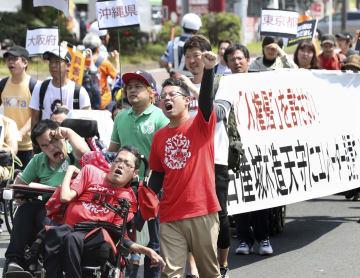 名古屋城天守閣の木造復元事業を巡り、エレベーター設置を求めデモ行進する参加者=19日午後、名古屋市