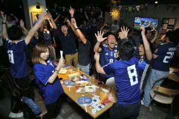 日本の勝利が決まり、歓喜に沸くサッカーファンら=19日、八戸市の「soul child」