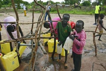 ウガンダ北部の難民居住区で水くみをする南スーダン難民の子どもたち=5月(共同)