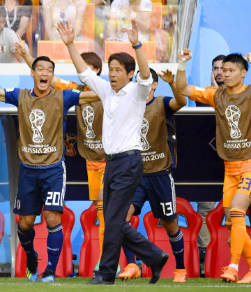 サッカーW杯1次リーグの初戦でコロンビアを破り、両手を上げて喜ぶ日本代表の西野朗監督(中央)=19日、ロシア・サランスク(共同)