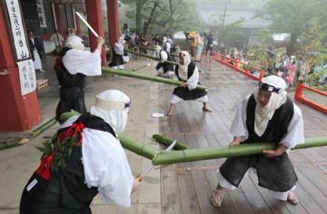雨の中、大蛇に見立てた青竹を刀で切る僧兵姿の男性たち(20日午後3時、京都市左京区・鞍馬寺)
