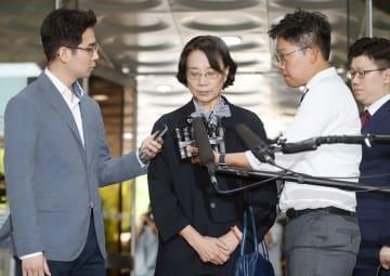 ソウル中央地裁に出頭し、記者団の質問を受ける李明姫氏=20日(聯合=共同)