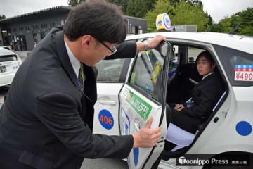6月に入社した大川さん(奥)に接客指導をする成長タクシーの指導員・天野さん(手前)=13日、青森市