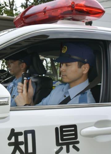 高知県警が試験導入するサイレンの音を変化させる機器のスイッチを手にする警察官=21日午後、高知市