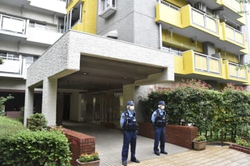 男女3人が殺傷された集合住宅前に立つ神奈川県警の警察官=21日午前、横浜市旭区