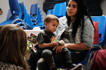米テキサスの施設で息子と座る、メキシコ国境を越えてきた女性=21日(ゲッティ=共同)