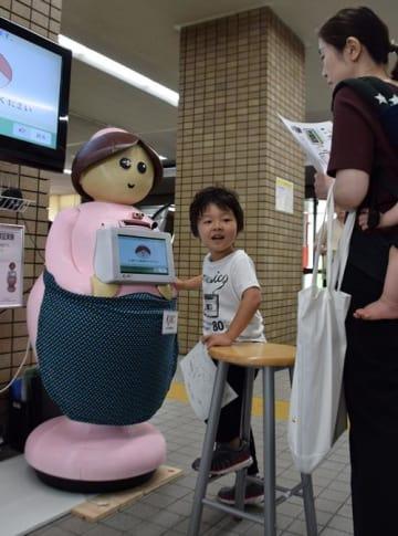 おもてなしロボット「D―hat(ディーハット)」を利用する来庁者の親子=21日、柏市役所