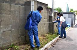 小学校のブロック塀を調査する尼崎市教育委員会の職員=19日午前、尼崎市西難波町6