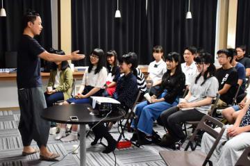 土屋さん(左)の講演を笑顔で聴く参加者たち