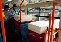 初めてのバス輸送で、郵便物が入った専用箱を座席に置く郵便局員。3箱分の6座席が確保されている=宍粟市山崎町鹿沢
