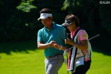 首位に浮上した池田勇太 キャディを務める女子プロの山口春歌とグータッチ(撮影:鈴木祥)