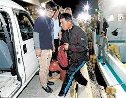 55良福丸で無事に気仙沼港に到着し、用意された車に乗り込む第68広漁丸の乗組員=22日午前3時15分ごろ