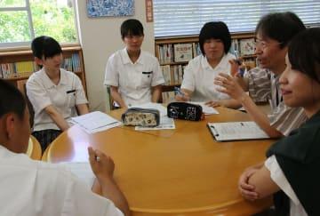 市医療統括官の桑原さん(右から2人目)らに、対馬の医療問題について取材する生徒=対馬高