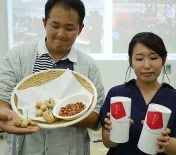 水田だった畑で収穫した高級落花生とナッツ菓子を手にする龍谷大農学部の学生(京都市左京区)