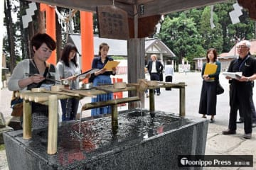 実演役と説明役に分かれて、手水のやり方を示す英語を確認する参加者たち