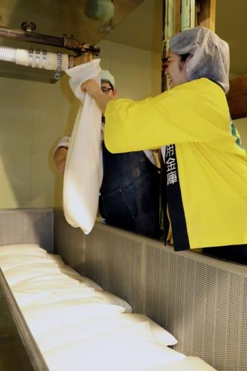 曙酒造で日本酒の搾り作業をする信金の若手職員=23日午前、福島県会津坂下町