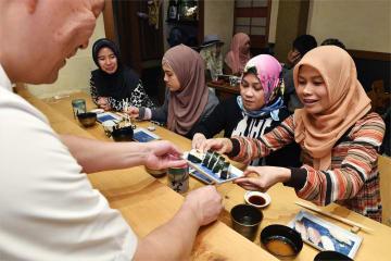 試食会でイスラム教の戒律に基づく「ハラル」に配慮したすしを楽しむ参加者ら=1月、福岡市