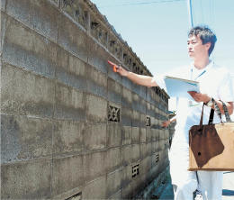 ブロック塀を点検する市職員=22日、大崎市古川