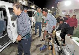 順洋丸で気仙沼港に到着し、用意された車に乗り込む第68広漁丸の乗組員=22日午前2時30分ごろ