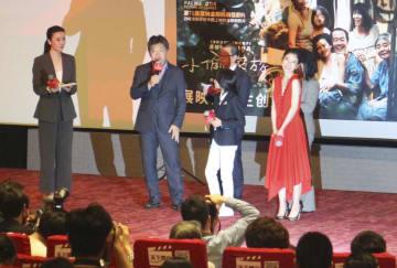 23日、中国上海の映画館で「万引き家族」の舞台あいさつをする是枝裕和監督(左から2人目)(共同)