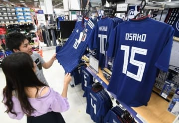 サッカー日本代表のユニホームを手に取る買い物客=鹿児島市のスポーツデポ・フレスポジャングルパーク店