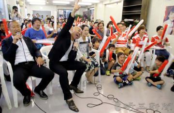 ゴルゴ松本さん(左から2人目)、元ラグビー日本代表の伊藤剛臣さん(左)らと共に盛り上がるパブリックビューイングの会場=23日午後、熊谷市の熊谷駅ビル「アズ熊谷」屋上特設会場