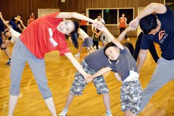 畠山さん(左)と柔軟体操をする子どもら