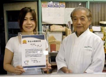 地元商工会が贈った認定書を手に笑顔の「菓舗 讃岐屋」8代目、永松麻那さん(左)と祖父の崇さん=宇土市