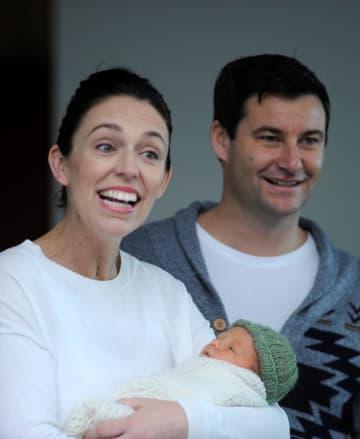 24日、長女を抱きニュージーランド・オークランドの病院を出るアーダン首相(左)とパートナーのクラーク・ゲイフォード氏(ロイター=共同)