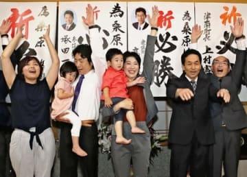 津南町長選で初当選し、子どもを抱いて万歳する桑原悠氏(中央)=24日午後8時すぎ、津南町下船渡己