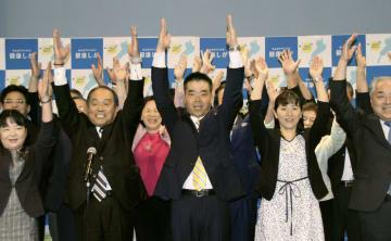 滋賀県知事選で再選確実とし、支援者らと万歳三唱する現職の三日月大造氏(中央)=24日夜、大津市
