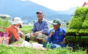 作業の合間の休憩で笑みを浮かべる西郷営農代表の種子田さん(中央)と湯田さん(右)=24日午前、えびの市西郷