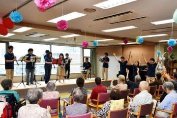 お年寄りを前に演奏を披露する日産自動車吹奏楽団の楽団員ら=厚木市中町