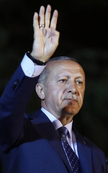 24日、トルコのイスタンブールで支持者らに手を挙げて応えるエルドアン大統領(AP=共同)