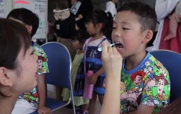 歯科衛生士から歯磨き指導を受ける子ども=新上五島町石油備蓄記念会館