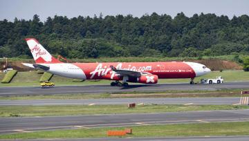 滑走路上で停止し、車両に引かれて移動するインドネシア・エアアジアX機=25日午前9時12分ごろ、成田空港