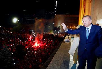 トルコ与党の公正発展党本部のバルコニーで、集まった人々にあいさつするエルドアン氏=25日、アンカラ(ゲッティ=共同)